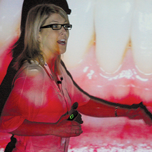 woman lecturing in front of an image of teeth and gums