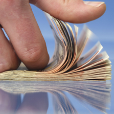 image of a hand flipping through dollar bills