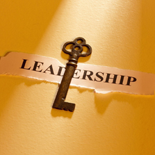 "key sitting on top of a piece of paper with the word ""leadership"" written on it"