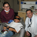 Dr. Judson Werner, a dental hygienist, and a young patient in a dental chair